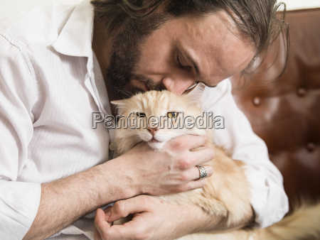 man cuddling with his maine coon