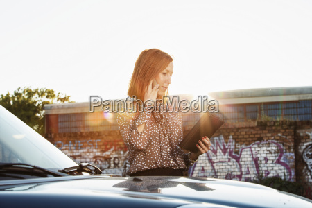 businesswoman with file standing behind parked