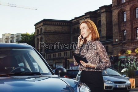 portrait of businesswoman with file standing