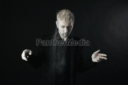 man wearing black clothes shaking off