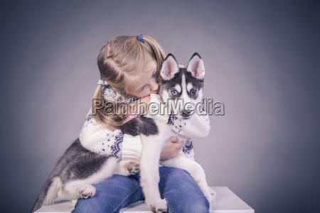 blond girl holding husky puppy on