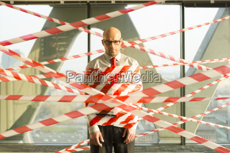 businessman tangled in barrier tape