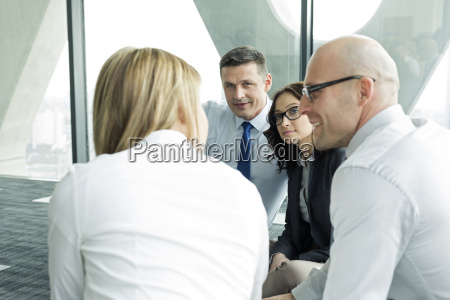 businesspeople sitting on floor discussing