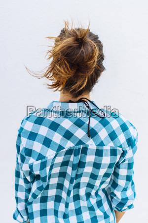 young woman wearing checkered shirt rear