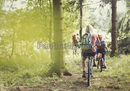 family mountain biking on trail in