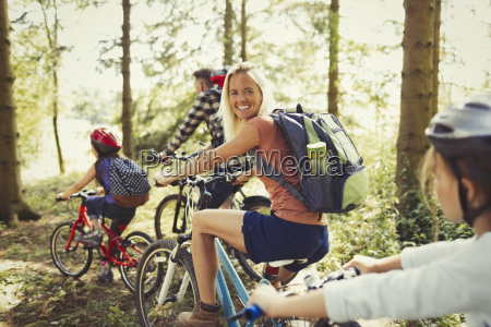 portrait smiling mother mountain biking with