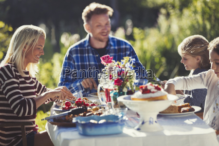 family eating at sunny garden party