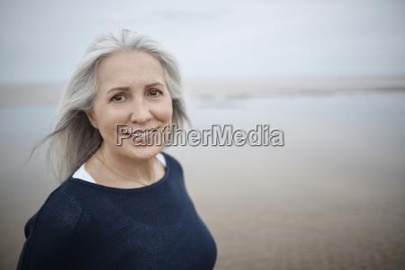portrait smiling senior woman on beach