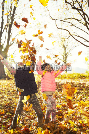 playful sisters throwing autumn leaves in