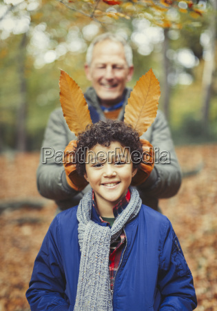 grandfather holding autumn leaves behind grandson