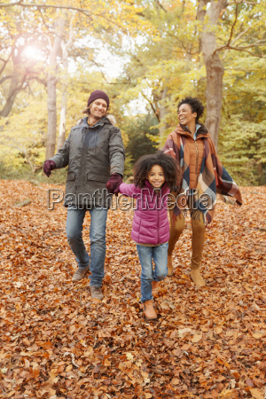 young family holding hands walking in