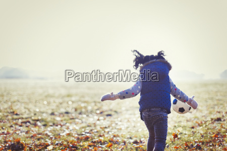 girl playing soccer in sunny autumn