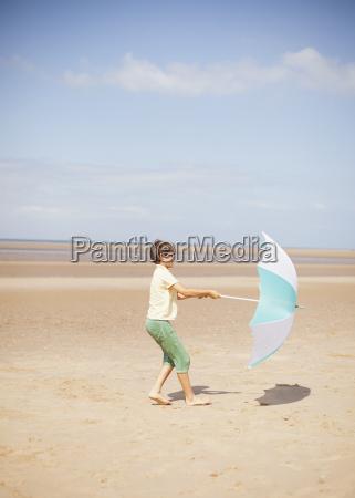 wind pulling umbrella in hands of