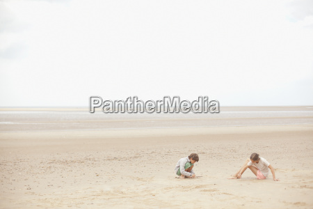 brother and sister playing in sand