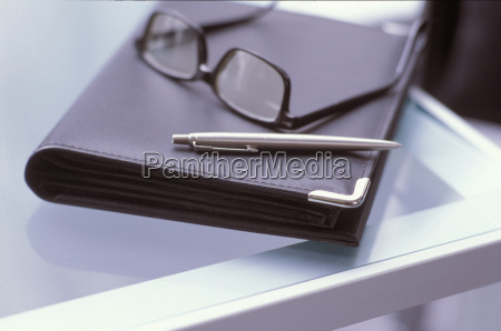 spectacles and diary on table
