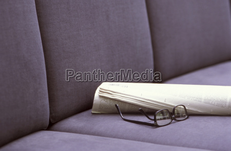 eyeglasses and newspaper on seating