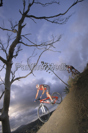 men riding mountain bike at dusk