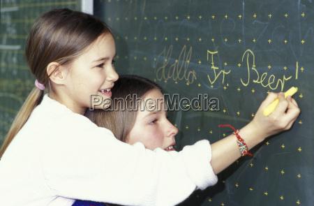 girls writing on blackboard