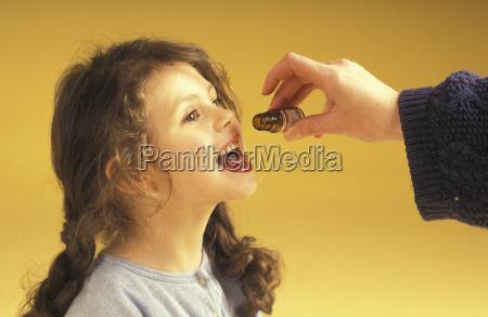 little girl getting medicine