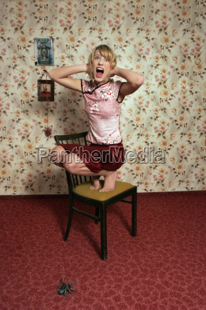 young woman screaming with spider on