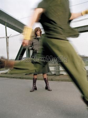woman standing on bridge man running