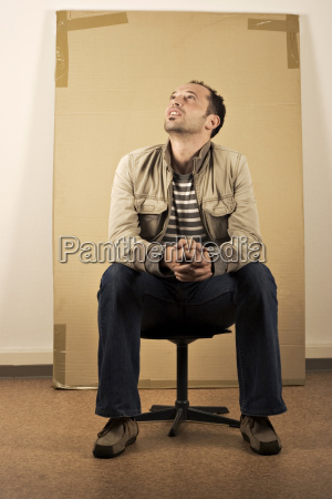 mann sitting in front of carton