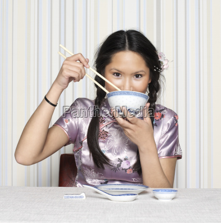 young woman eating with chopsticks portrait