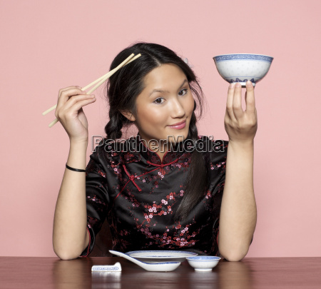 young woman holding chopsticks and bowl