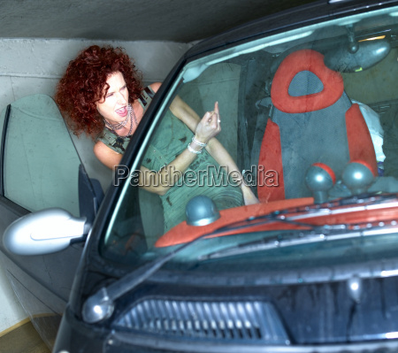 woman entering car making rude hand