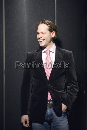 young businessman laughing hand in pocket