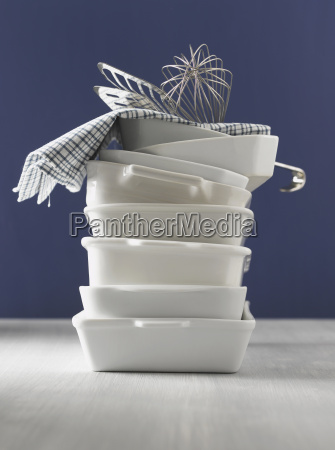 stacked casseroles dishcloth eggbeater and fish