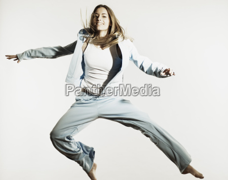 young woman in sportswear jumping against