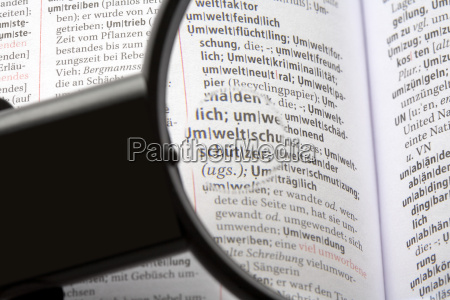 magnifying glass on encyclopedia close up