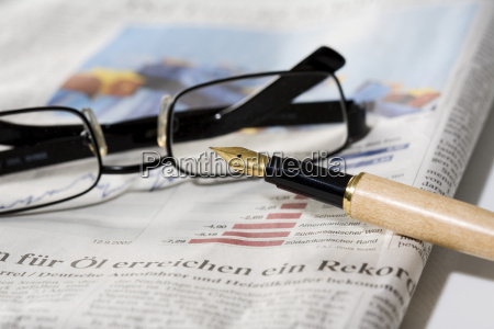 pen and spectacles on newspaper close