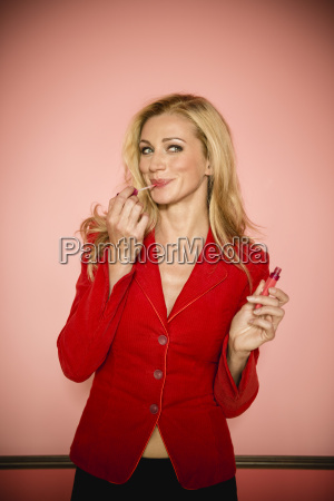 germany stuttgart businesswoman applying lipstick close