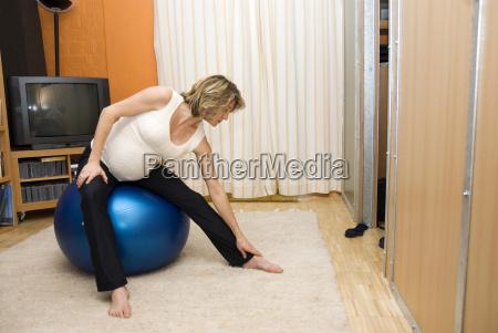 pregnant woman sitting on gymnastics ball