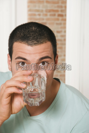 man drinking a glass of