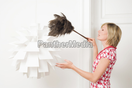 woman dusting a lamp with a
