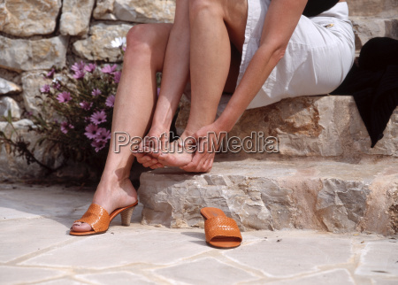woman sitting on stairs rubbing feet
