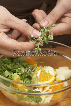 putting herbs into bowl close up