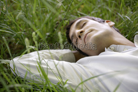 man sleeping in meadow close up