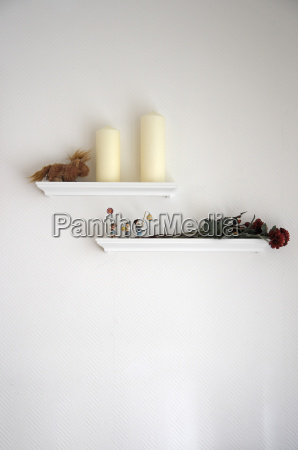 dried rose and candles on shelf