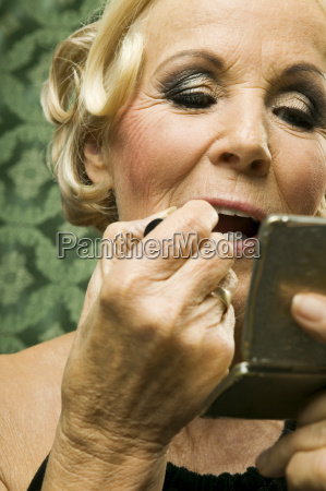 senior woman painting lips