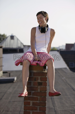 young woman sitting on chimney smiling