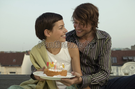 man giving birthday cake to woman