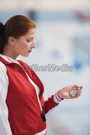 young woman holding stop watch