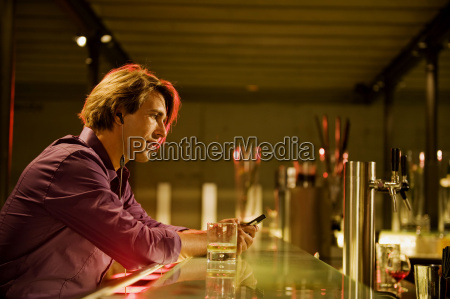 young man in bar wearing earphones