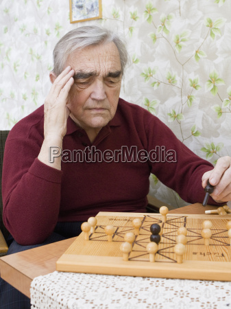 man playing board game with head