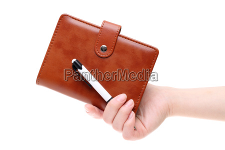 hand holding brown leather notebook isolated
