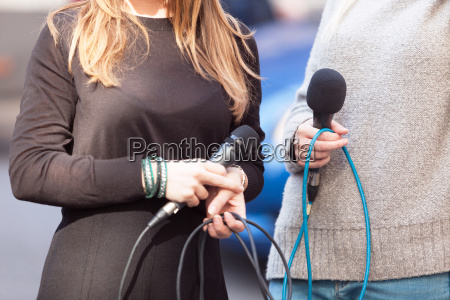 female journalists holding microphones waiting for